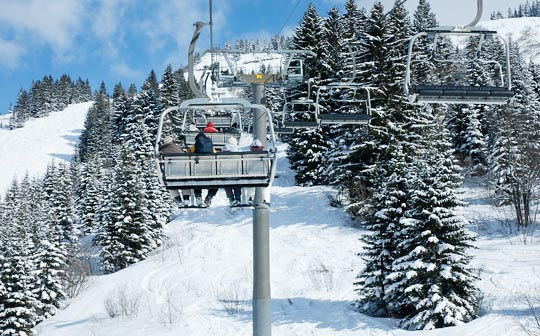 View   from chairlift of ski tracks between trees
