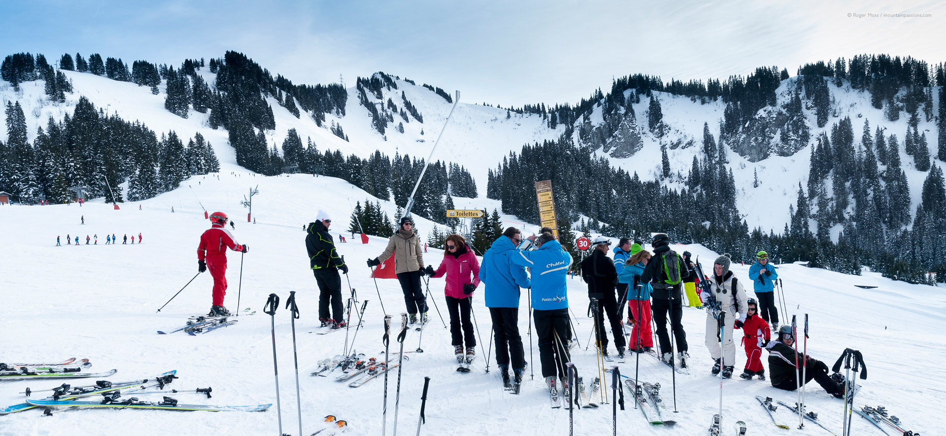 Group of skiers gathered beside pistes with mountains and forests in background at Chatel.