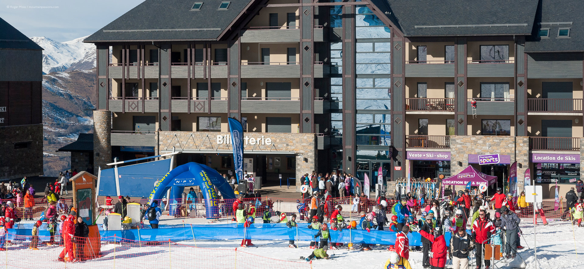 Skiers with beginner area and apartment buildings