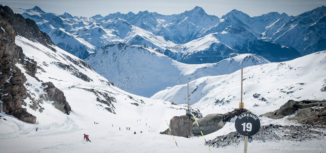 Overview of skier on La Sarenne black piste with big mountain views