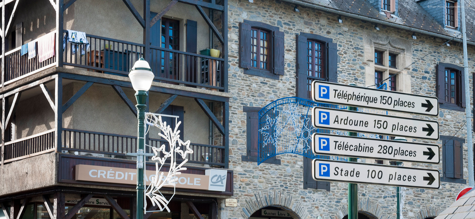 Low view of stone and timber facades, plus sign to ski lifts
