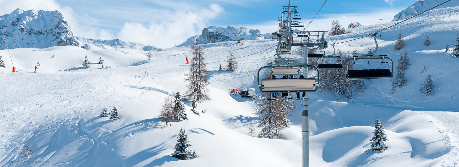 Wide overview from chairlift of pistes after fresh snow
