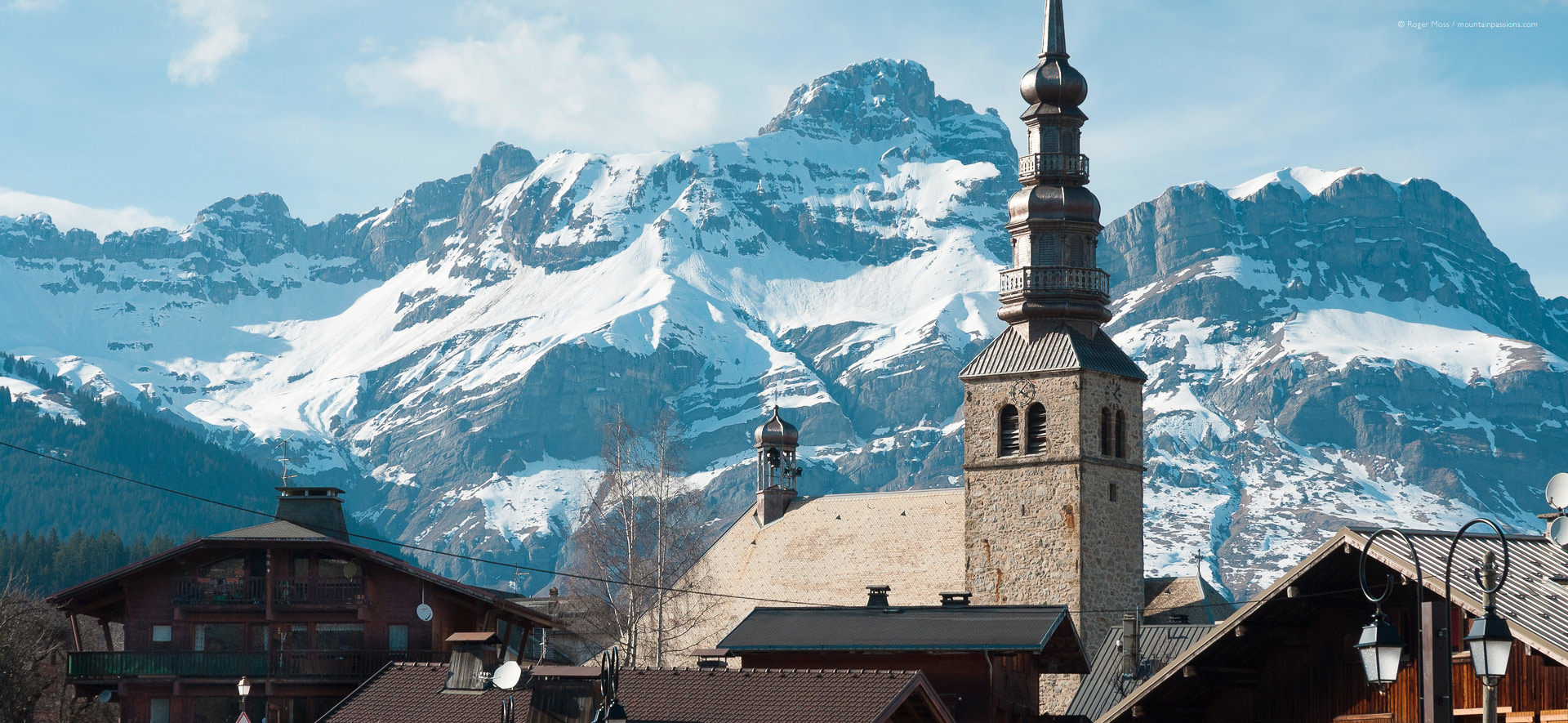 Chalet rooftops and village church at Combloux, with Mont Blanc in background.