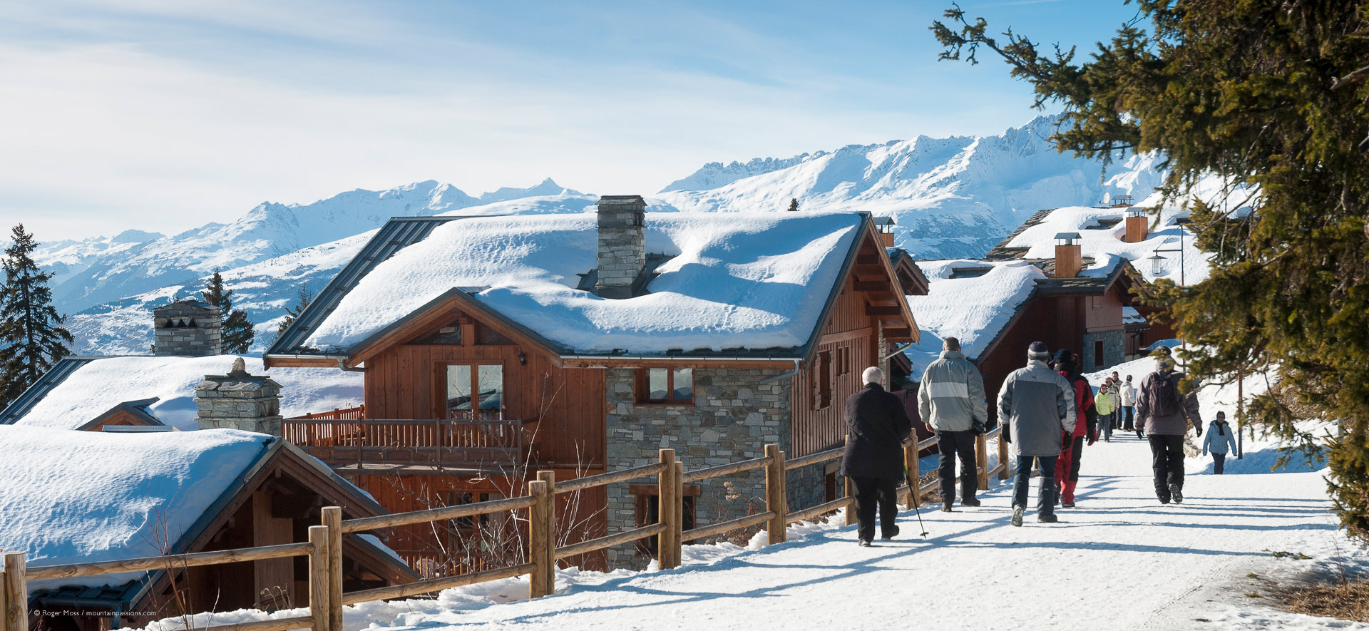 Late afternoon walkers on footpath with snow-covered chalets at La Rosiere.