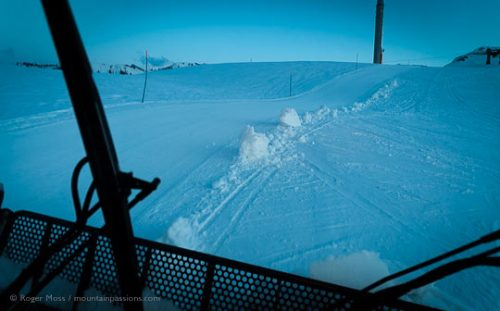 Driver's view from cab of groomer on ski piste at dusk