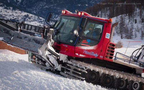 Piste groomer operator instruction, with mountain backdrop