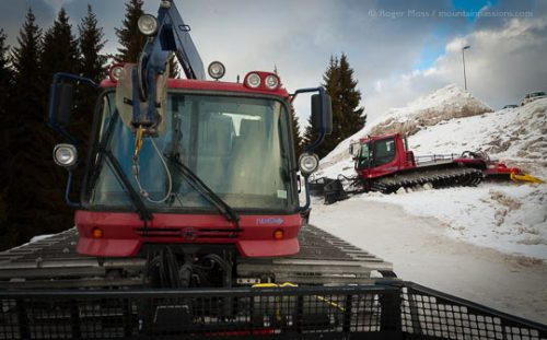 Two piste-groomers parked in snow