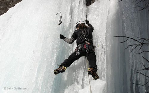 Ice climber on frozen waterfall