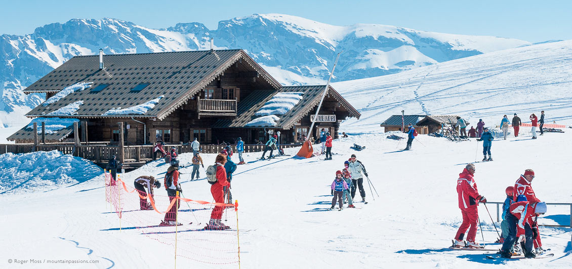 Young skiers with ski instructors beside mountain restaurant at Le Devoluy.
