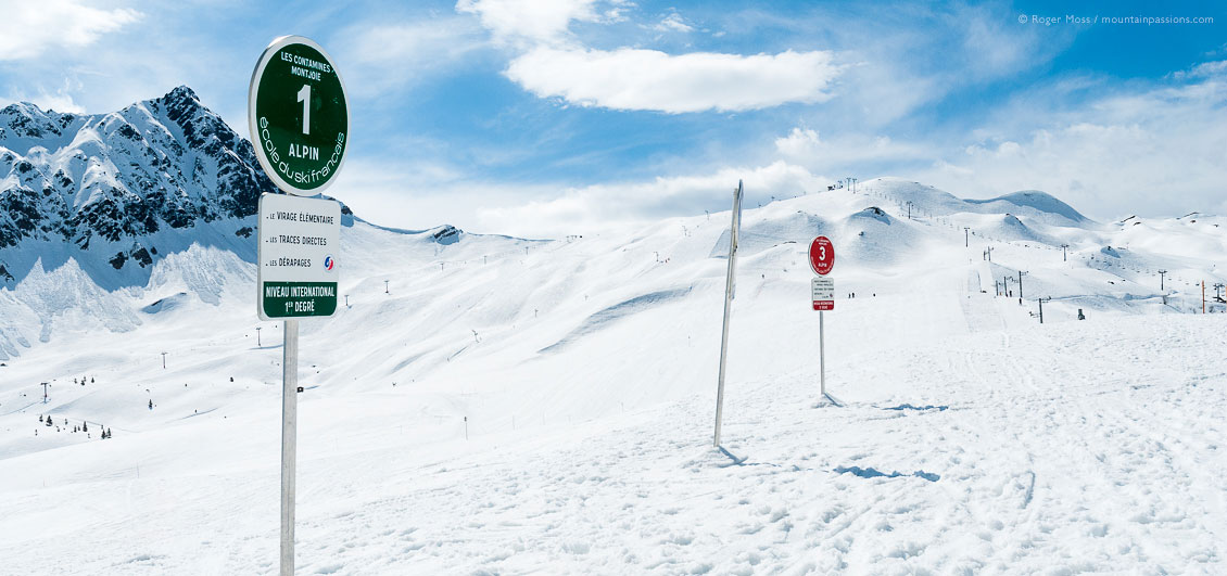 Wide view past ski school signs to mountains and pistes at Les Contamines