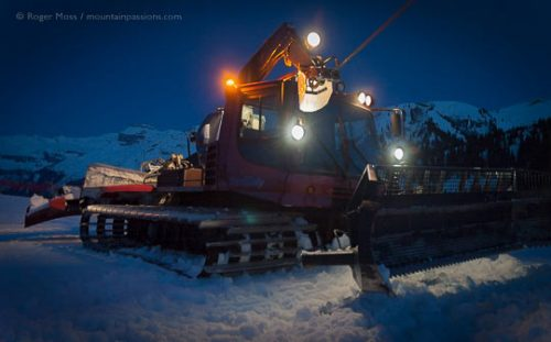 Night view of winch-equipped piste groomer with lights