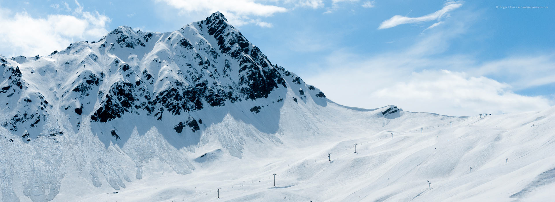 Long view of mountainside with ski lifts at Les Contamines