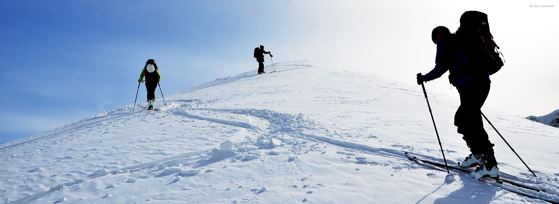 Low, wide view of ski-touring group nearing crest of mountain, French Alps