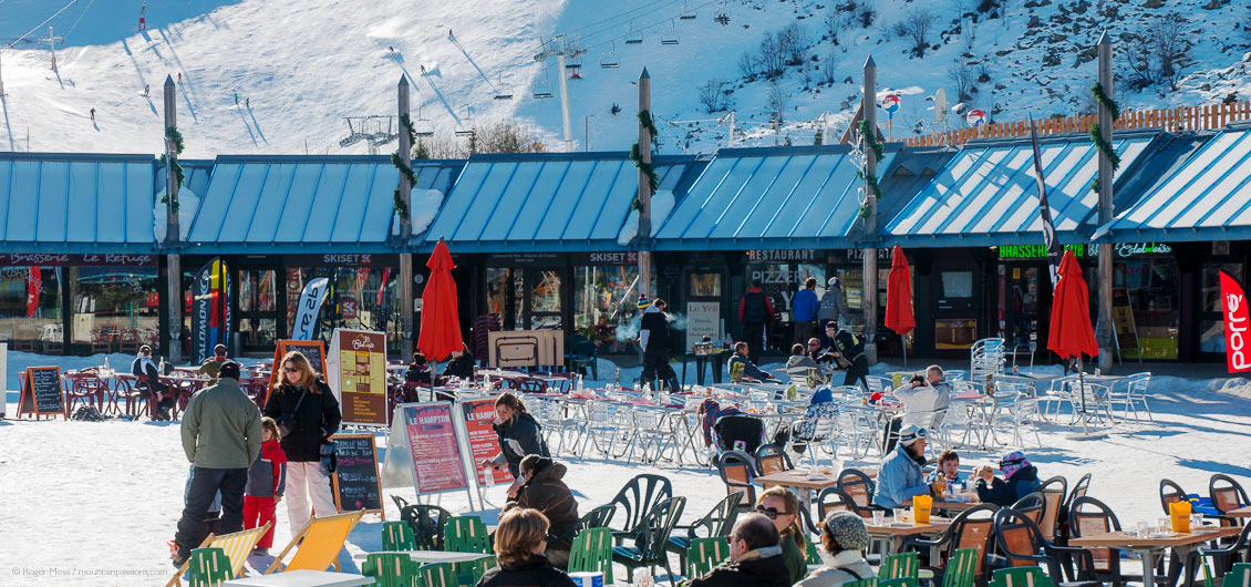 Visitors at cafe tables in centre of ski village at Piau Engaly