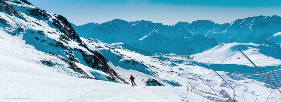 Wide view of skier on piste with mountains and Alped'Huez ski village in background.