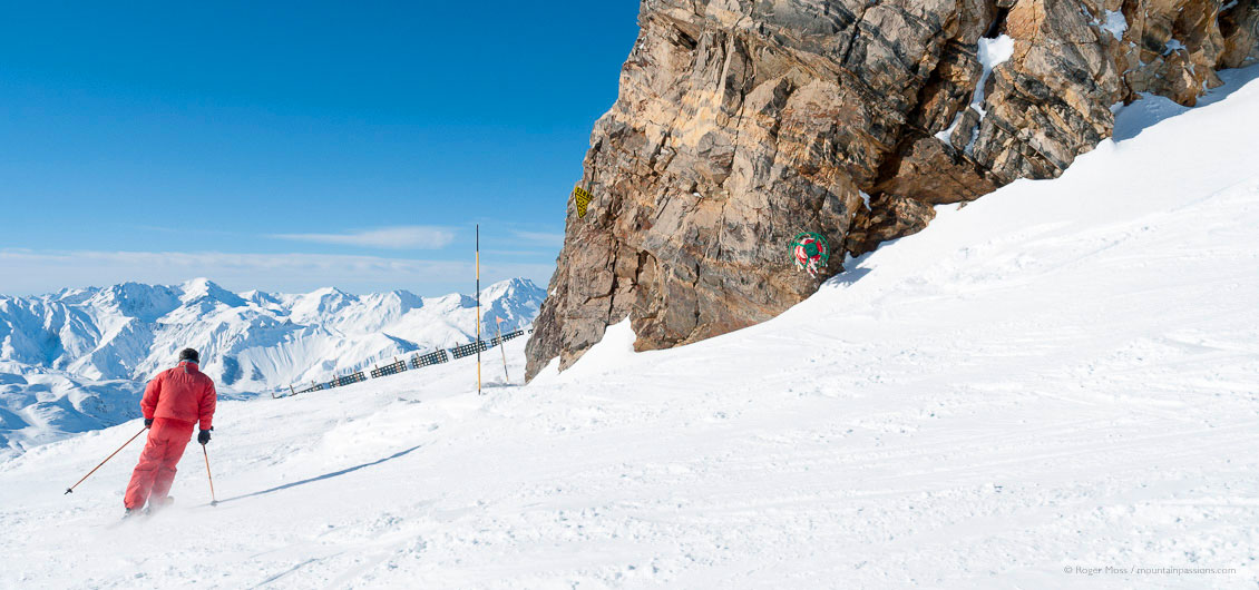 Lone skier passing rocky outcrop at la Saulire, between Courchevel and Meribel