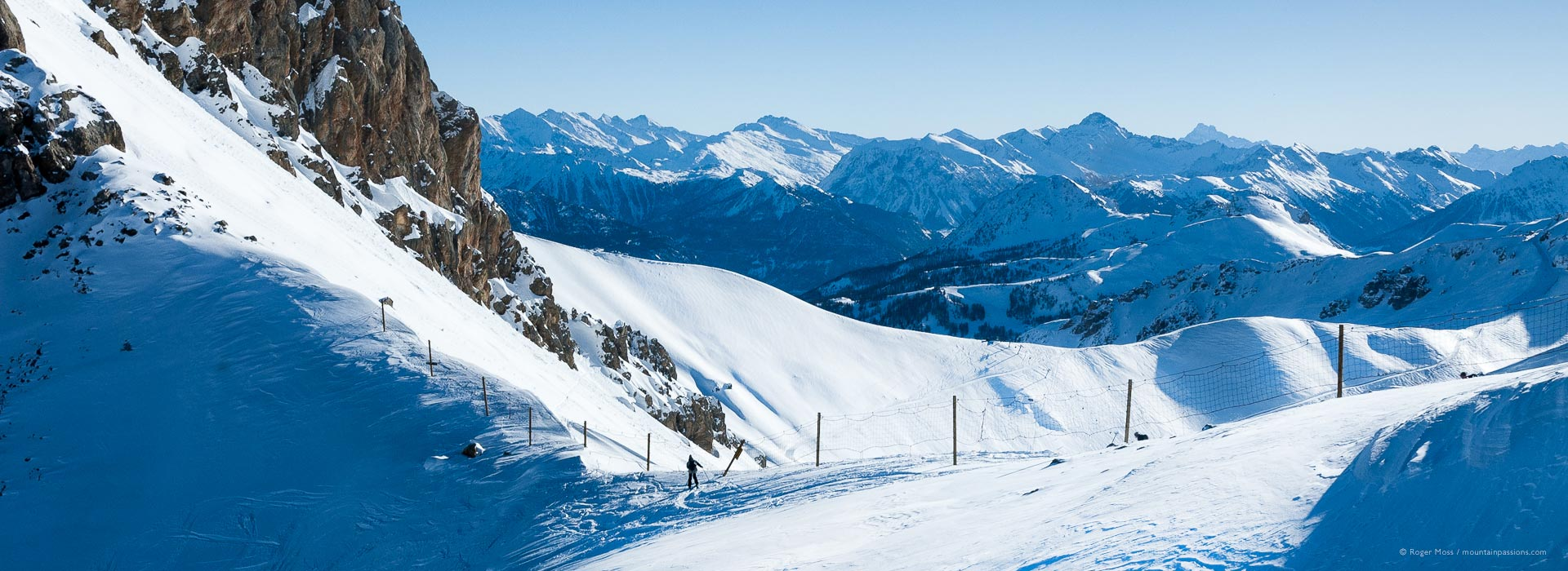 Long view of lone skier on snow-covered ridge with vast mountain background
