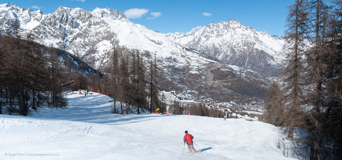 Skier on wide, tree-lined piste, with Puy Saint Vincent ski village below