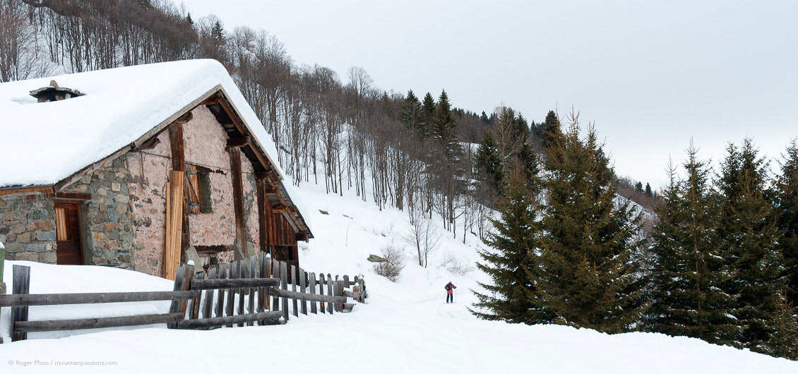 Lone skier on country trail passing mountain chalet, with forests