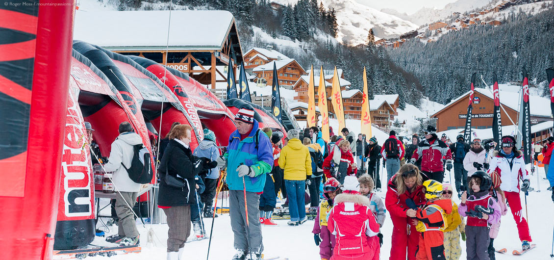 Skiers and other visitors at ski show with village and mountainside in background