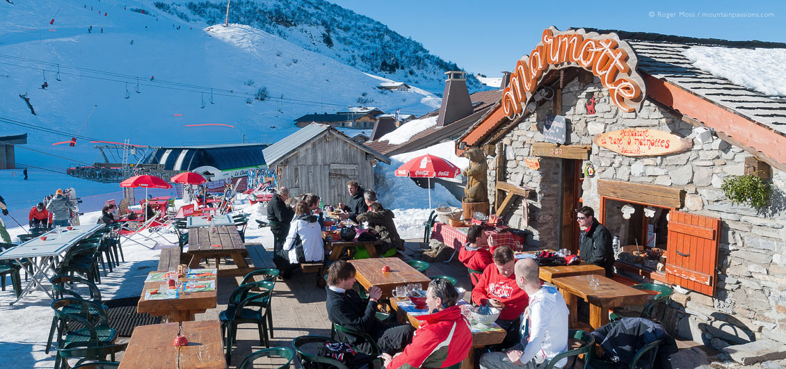 View of skiers in sunshine at mountain restaurant above Chatel, Portes du Soleil