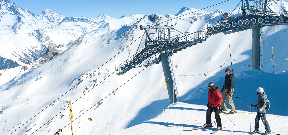 Overview of skiers leaving chairlift with mountains at Valfrejus ski resort, French Alps