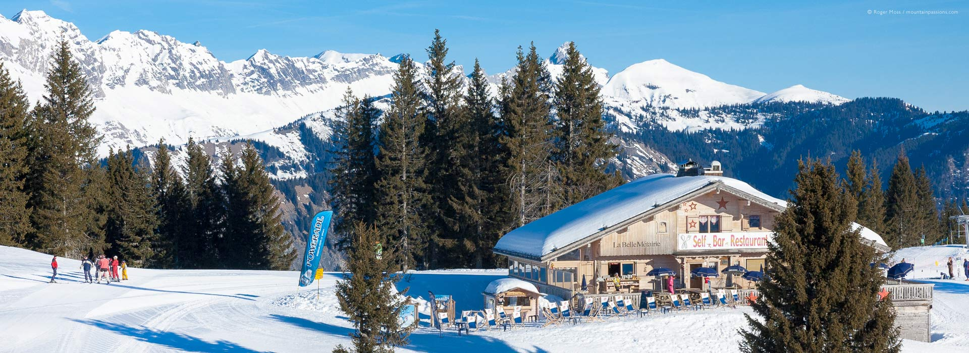 Wide view of early morning skiers beside chalet-style mountain restaurant above Crest Voland.