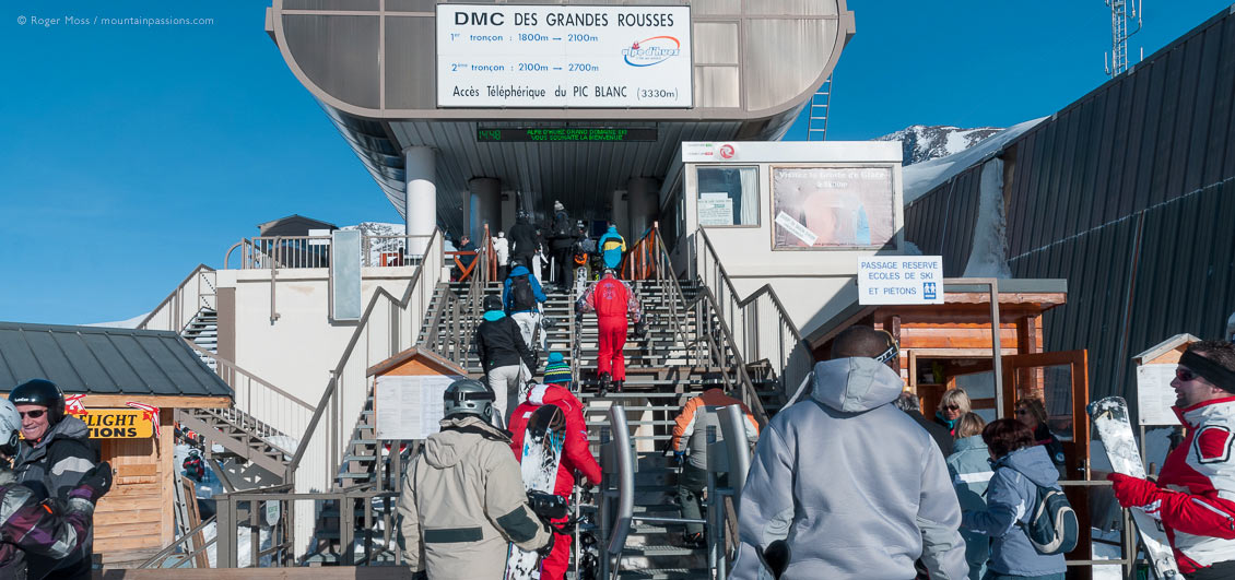 Skiers and snowbaorders climbing steps to gondola ski lift at Alpe d'Huez