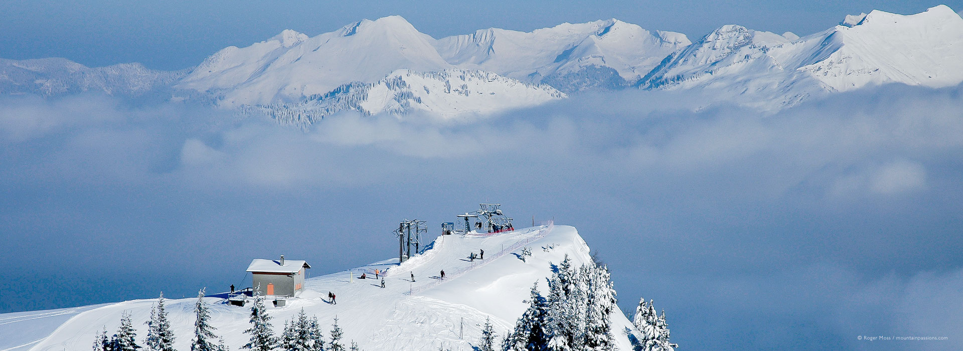 High view of chairlift with skiers, with mountains above clouds at Samoens