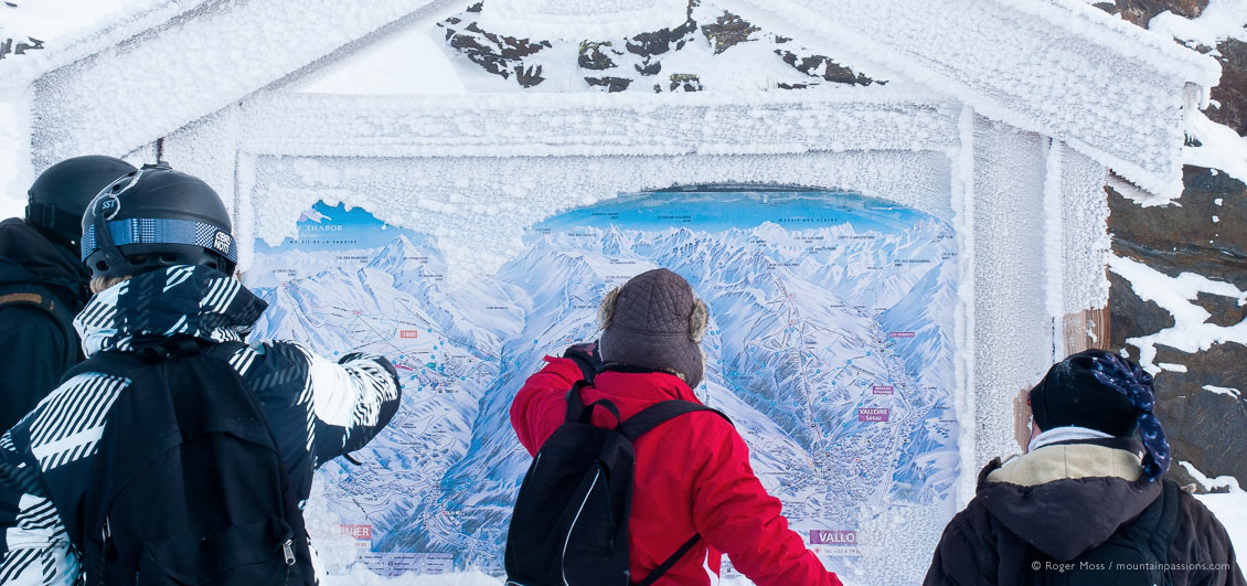 Group of skiers looking at snow-dusted piste map at Valloire ski resort