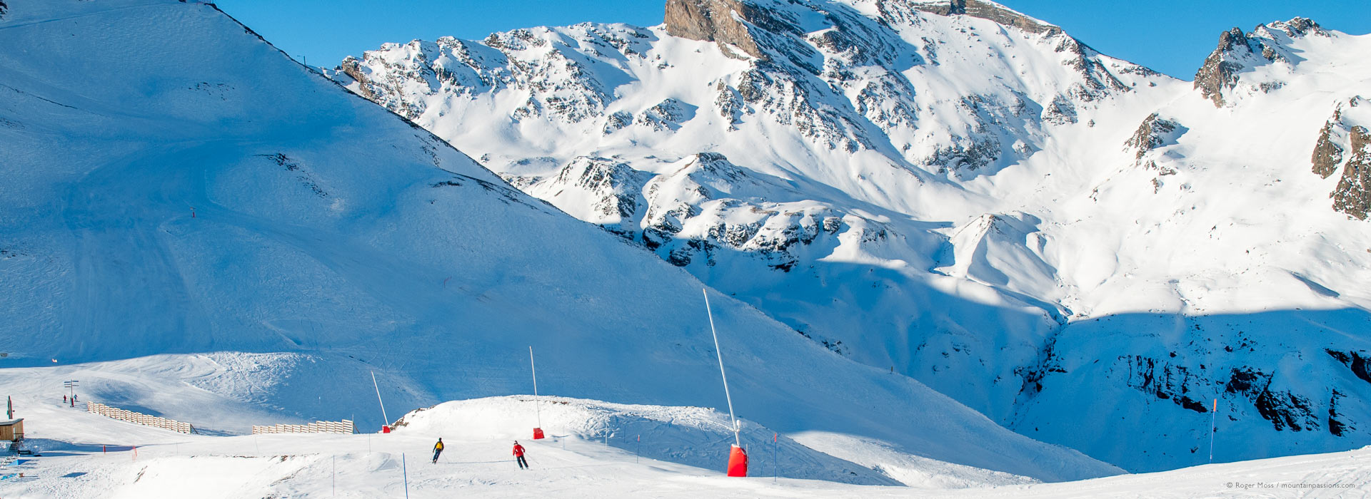 Wide view of mountains with skiers on piste above Piau Engaly.