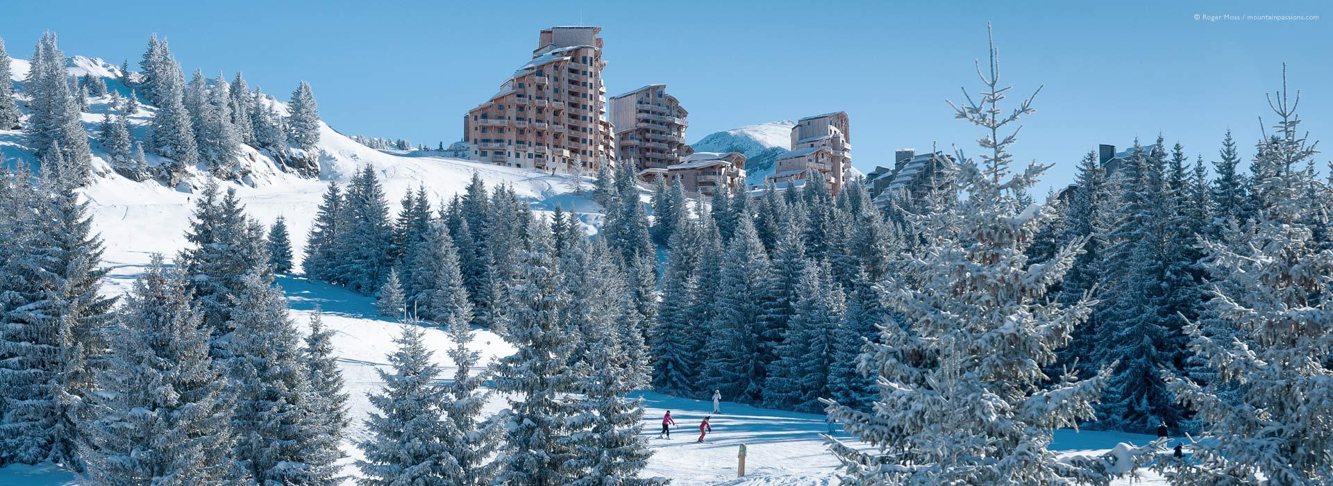 Skiers on tree-lined piste below Avoriaz ski resort