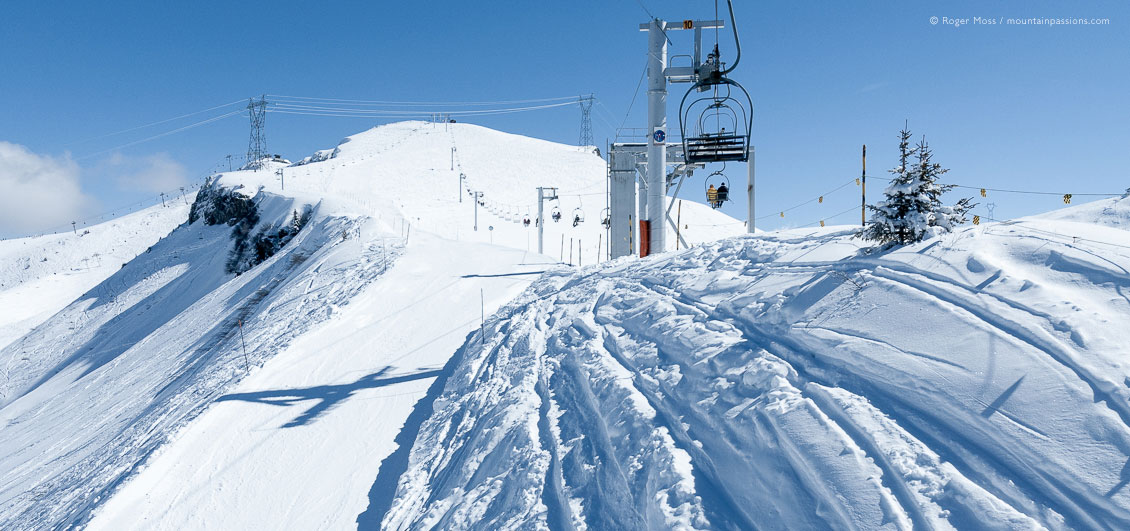 Wide view from chairlift of fresh snow and ski area above Les Carroz