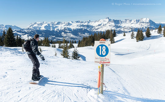 Rear view of snowboarder passing piste sign