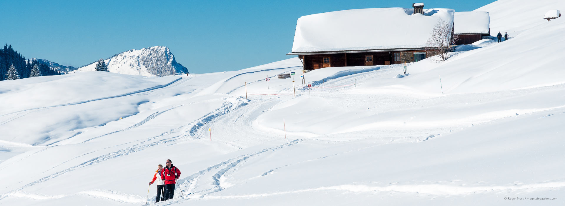Snow-shoeing on mountain with traditional chalet, La Toussuire, French Alps