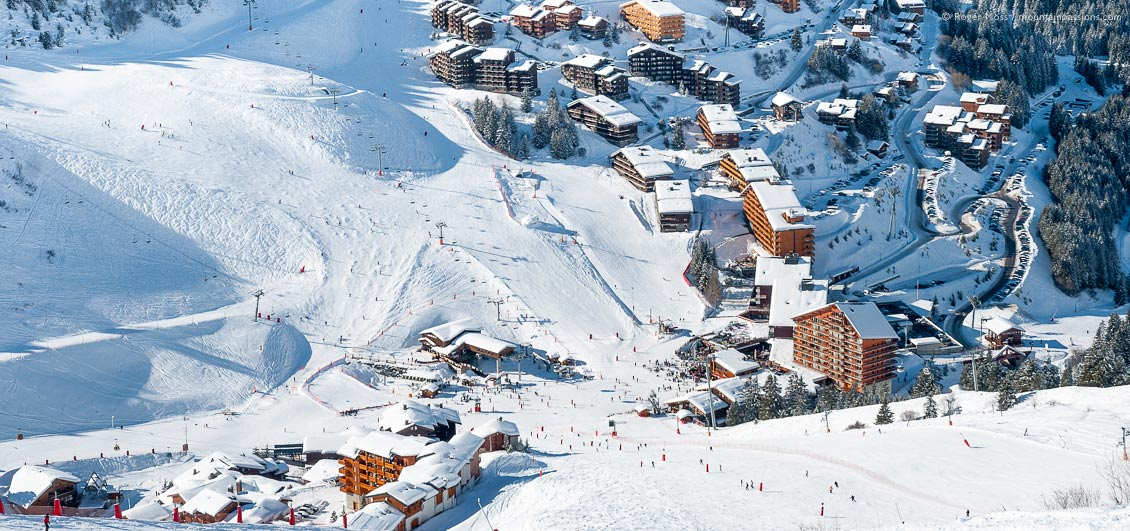 View from the mountainside of skiers at Meribel ski resort, French Alps
