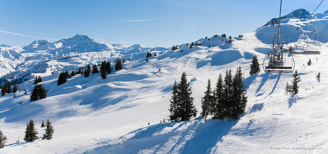 Wide view of ski area in sunshine from chairlift at Areches Beaufort
