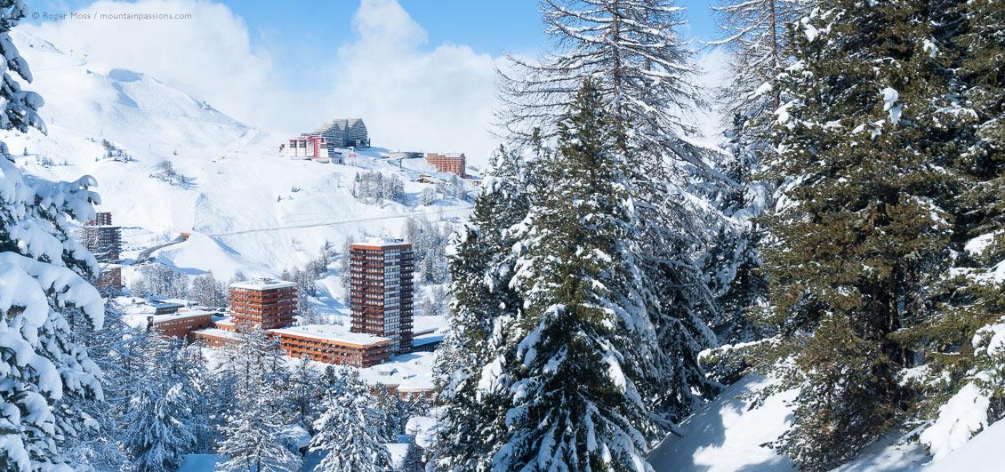 Elevated view through snow-covered trees of Plagne Centre ski village, La Plagne