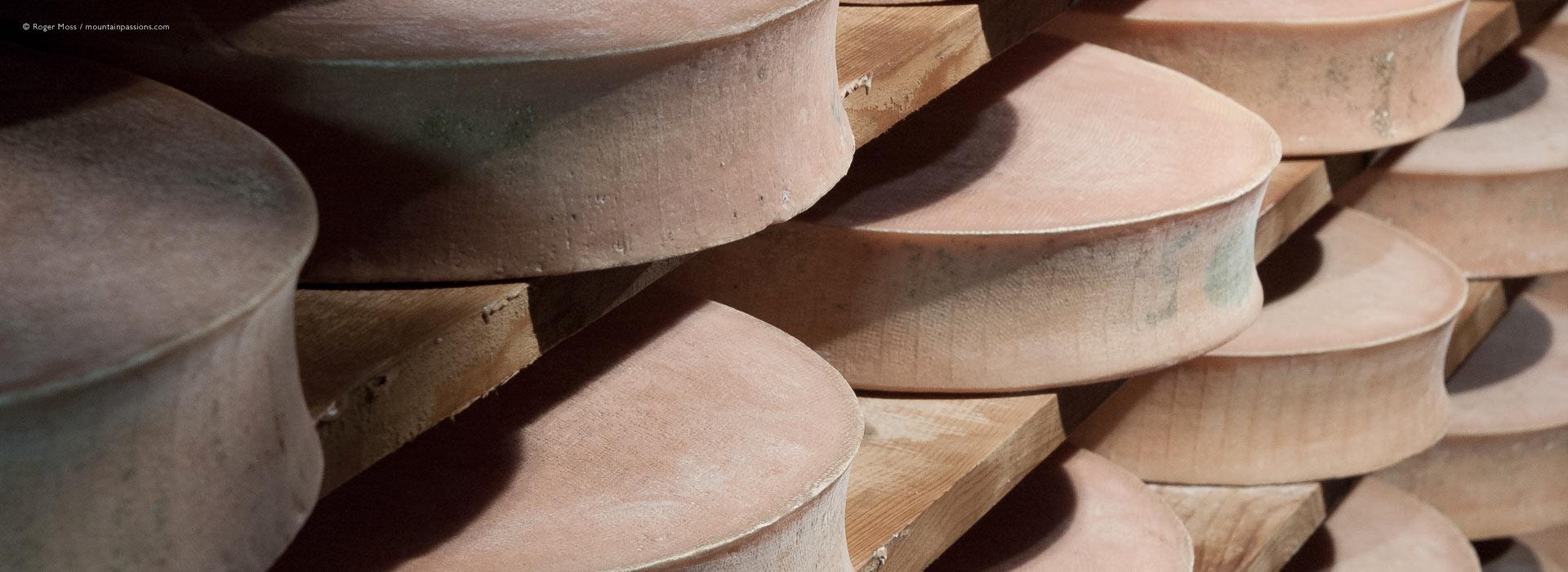 Beaufort cheeses maturing on racks