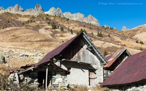 Group of abandoned chalets with iron roofs on mountainside in French Alps.