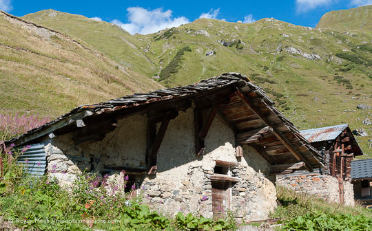 Abandoned stone-built mountain chalets with mountains