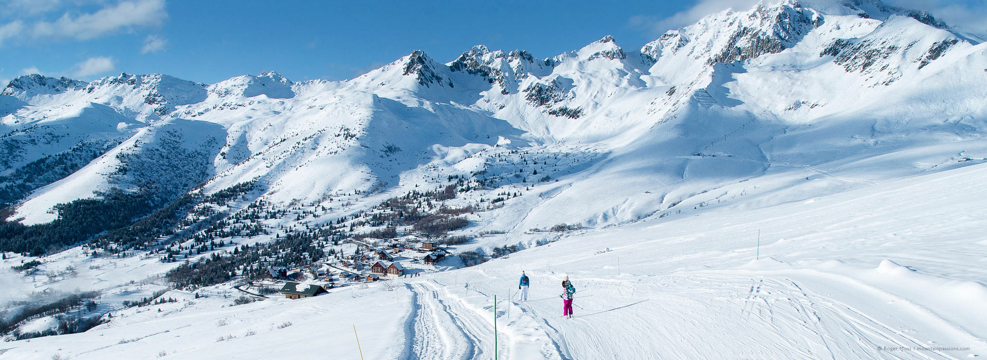 Wide view of skiers with deep snow above mountain village at Saint Francois Longchamp.
