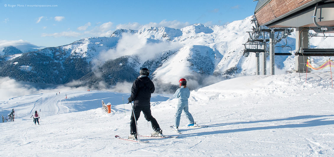 Family skiers beside high-speed chairlift at Saint Francois Longchamp