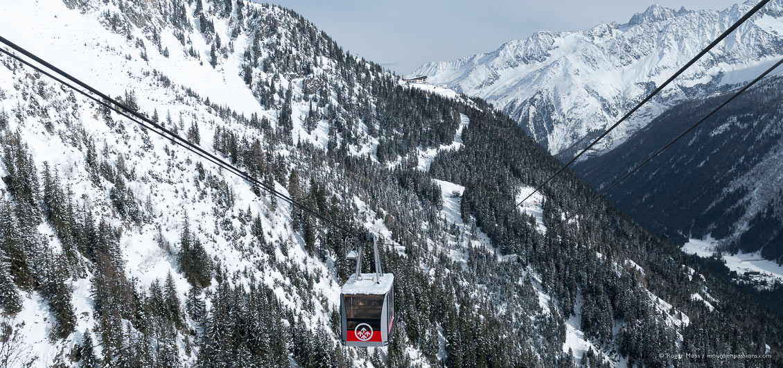 Wide view of cable-car crossing snow-covered valley, showing ski pistes and mountains.