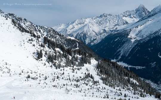 High view of ski pistes on mountainside with valley and mountains