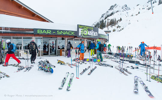 Wide view of skiers and skis outside mountain snack bar in Flegere ski area.