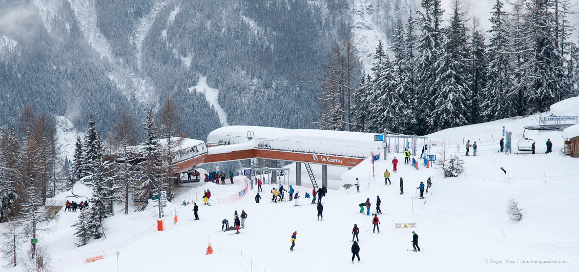 Overview of skiers converging on Le Cornu chairlift in Chamonix, with wooded mountainside