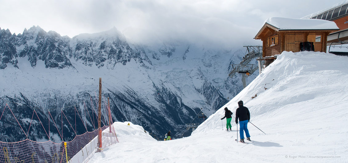 Two skiers starting piste beside chairlift, with clouds and snow-covered mountains.