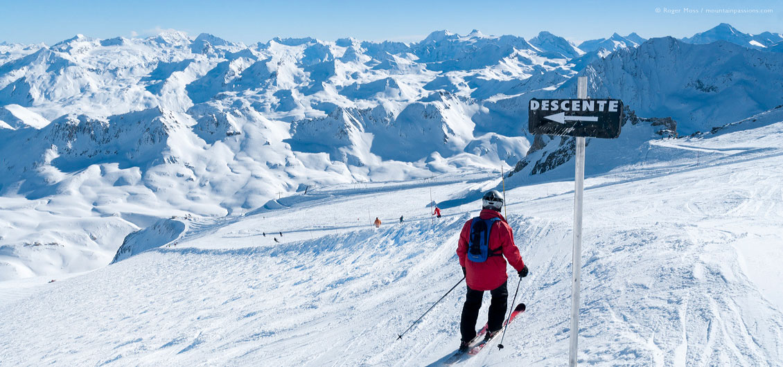 Wide view above glacier, showing skiers and mountain landscape