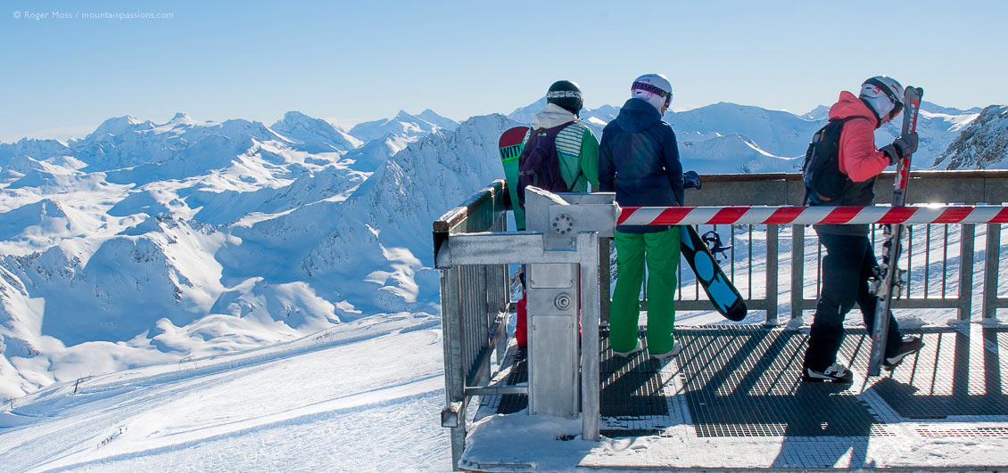 Skiers looking at glacier from platform of cable car at Tignes